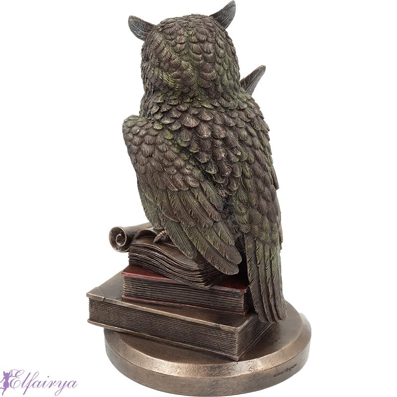 owl is sitting on books